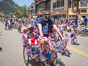 Man on decorated bike in 4th of July Parade