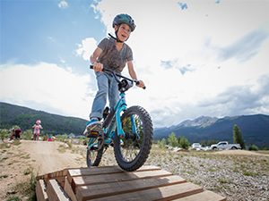 Boy riding on wooden feature in Frisco Bike Park
