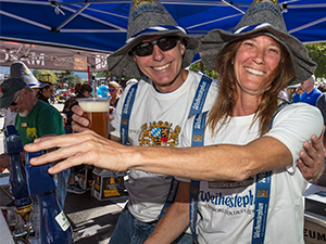 Man and woman dressed in Oktoberfest outfits pouring beer