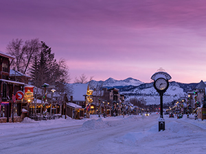 Frisco Main Street and Frisco clock with snow and purple sky