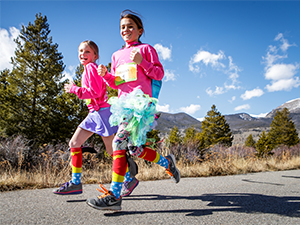 Two girls dressed up in costumes running in the Girls on the Run 5k