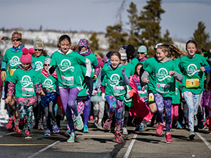 Group of girls running at start of Girls on the Run event