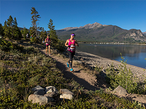 Woman running on trail by Dillon Reservoir at Run the Rockies trail race