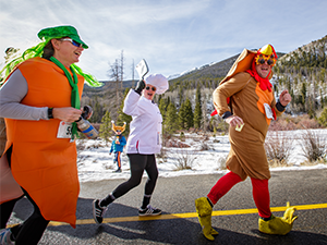 Group dressed up as turkey and chef running in Turkey Day 5k