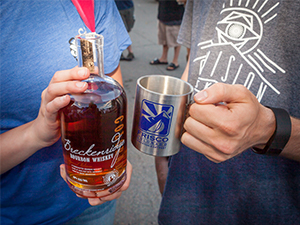 People holding bottle of whiskey and cup at Whiskey Tour at BBQ Challenge