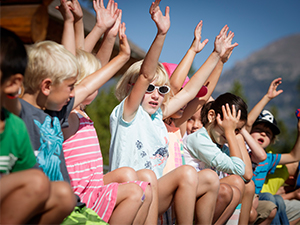Group of kids raising hands at youth camp