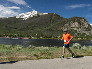 Man running on paved rec path with Dillon Reservoir and Peak One in background