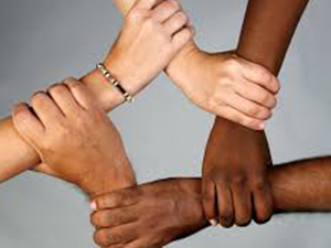 Five hands of different skin tones holding onto each other's wrists to form a circle